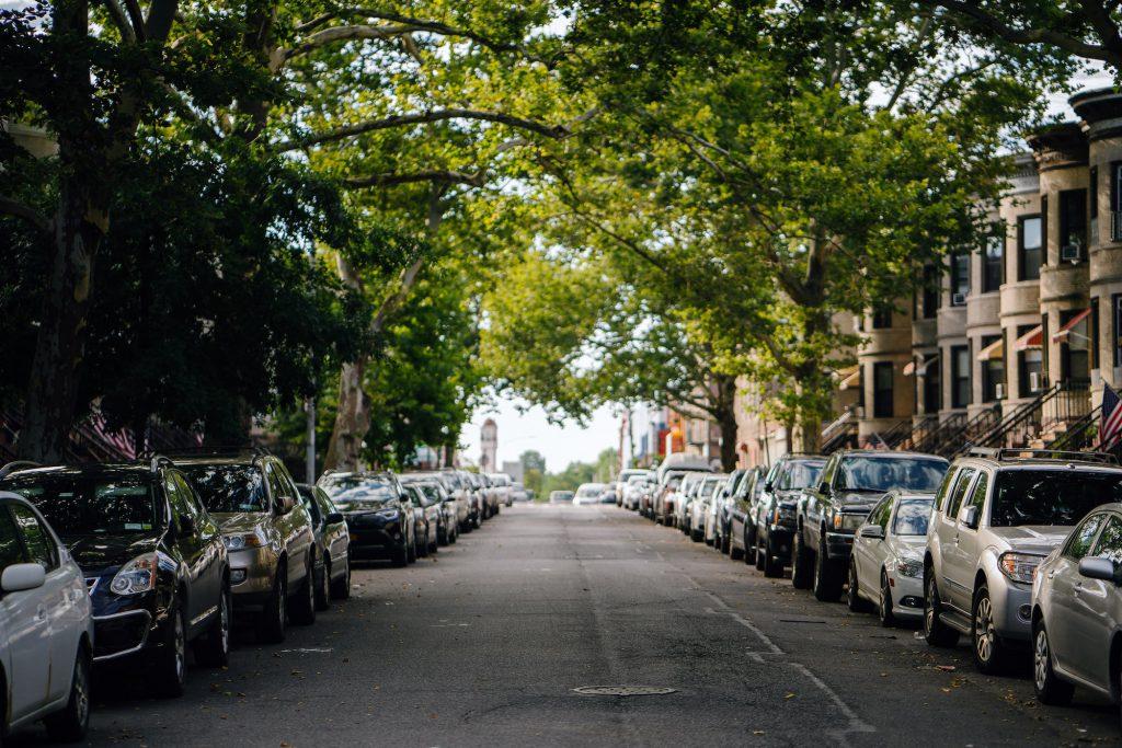 Rua bastante arborizada de uma cidade