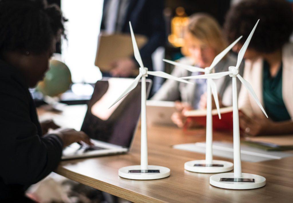 Mulheres trabalhando ao redor de uma mesa com maquetes de hélices para produção de energia eólica