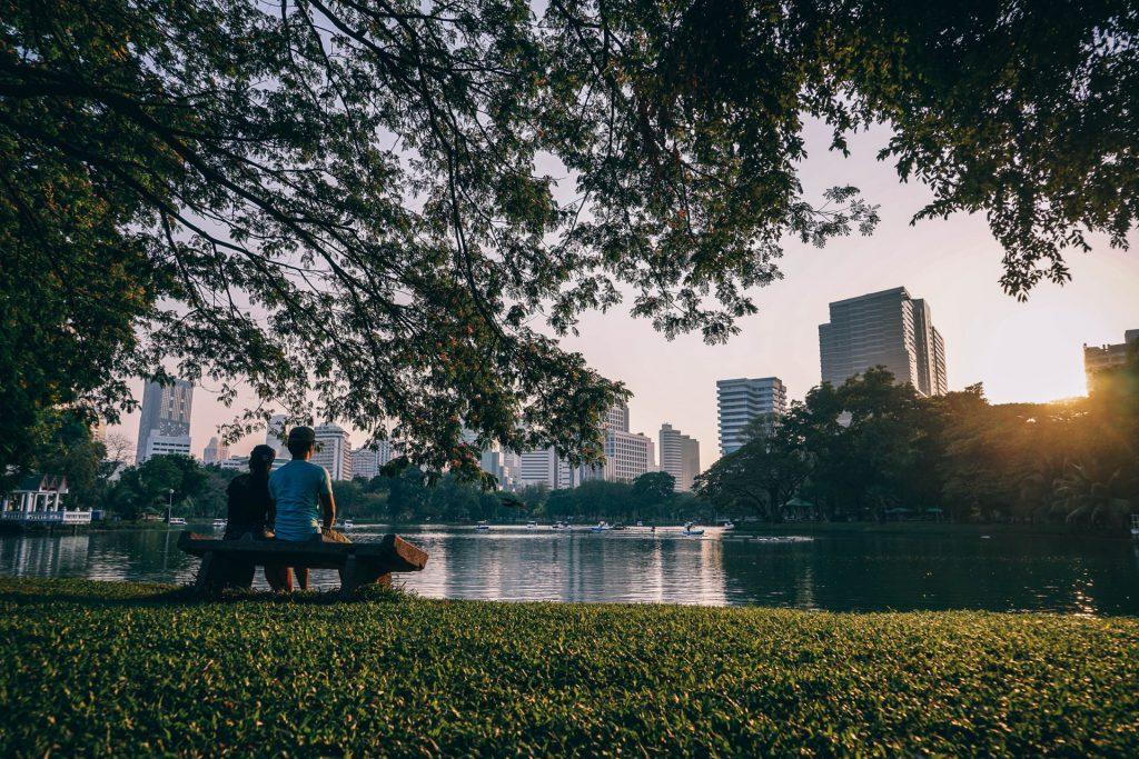 Casal sentado a beira de um lago em parque arborizado em área urbana