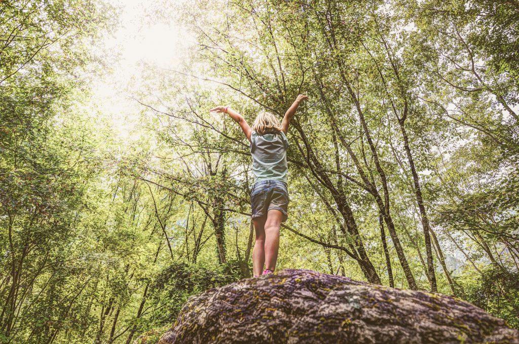 Garotinha de braços abertos cercada por árvores