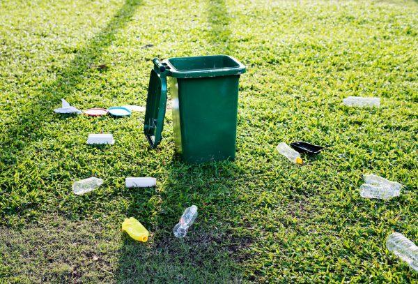 Área gramada com um lixeira aberta e várias garrafas no chão ao seu redor