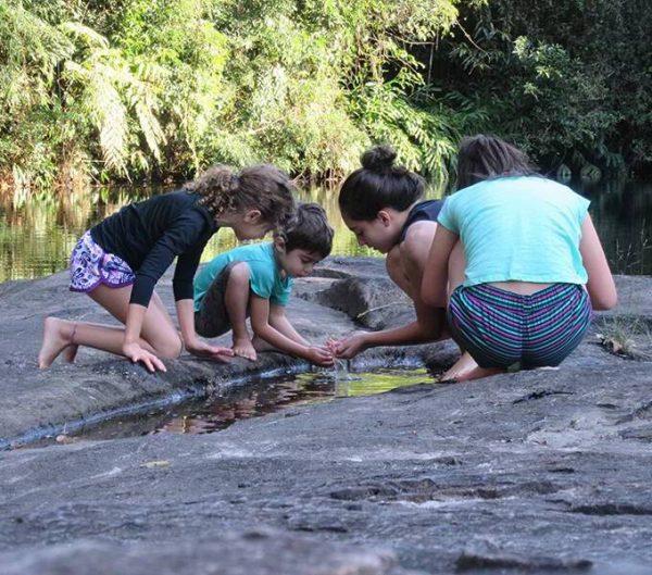 Crianças brincando na margem da riacho na RPPN Parque das Neblinas