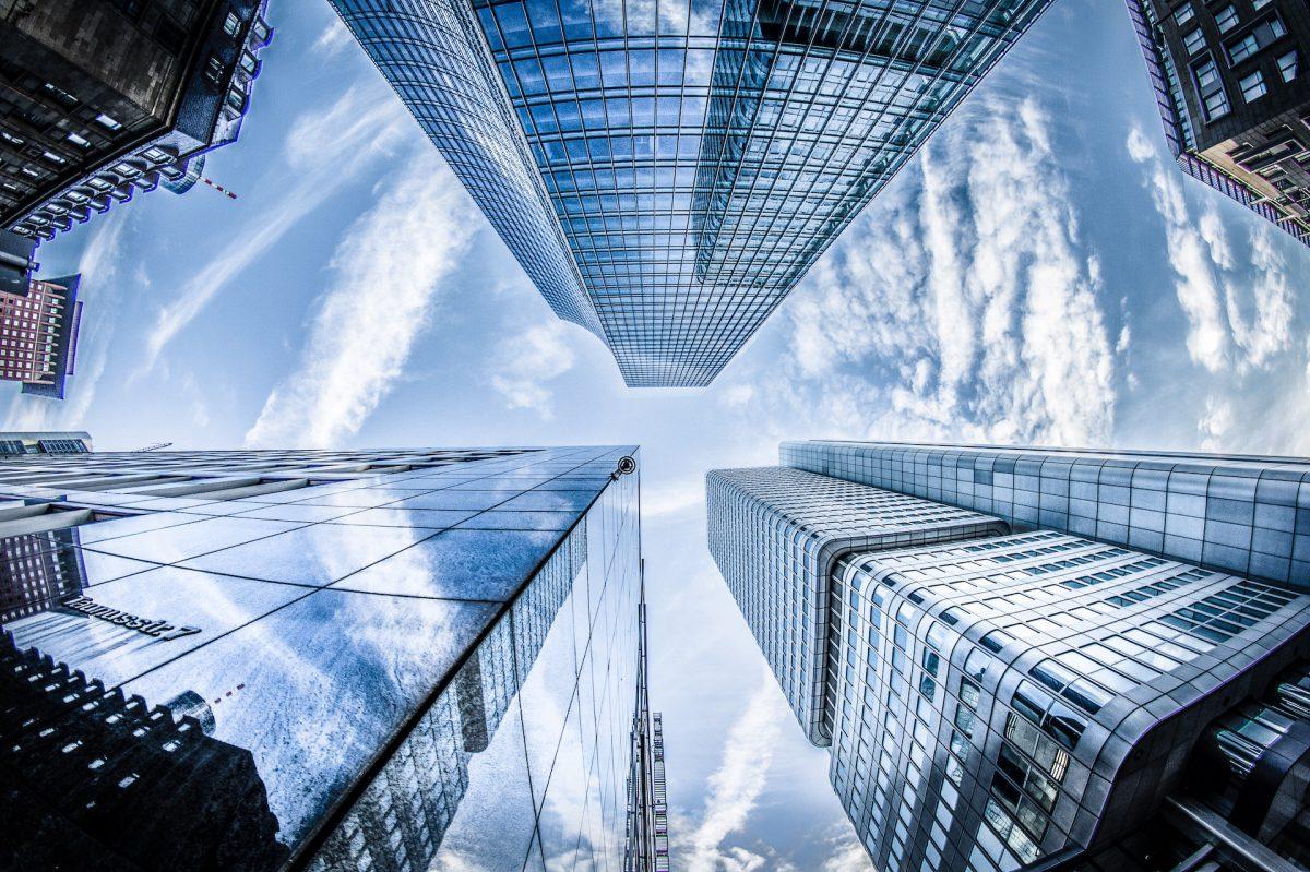 Prédio vistos de baixo para cima, com suas janelas de vidro refletindo o céu azul