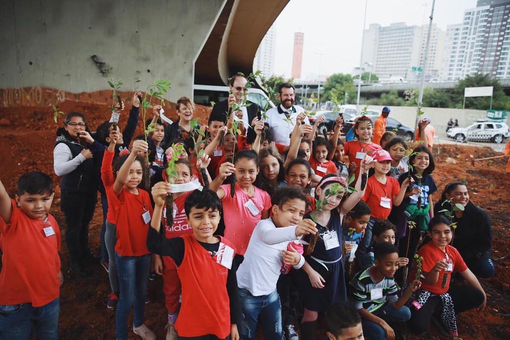 Grupo de crianças segurando mudas que iriam plantar em seguida no Bosque Bem-te-vi