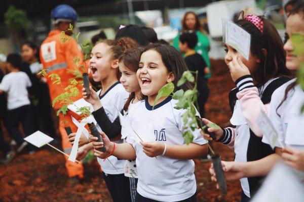 Crianças sorrindo com mudas de árvores nas mãos