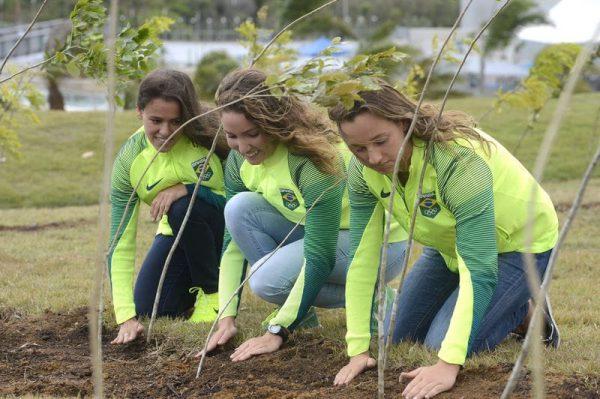 Três atletas brasileiras plantando mudas na Floresta dos Atletas