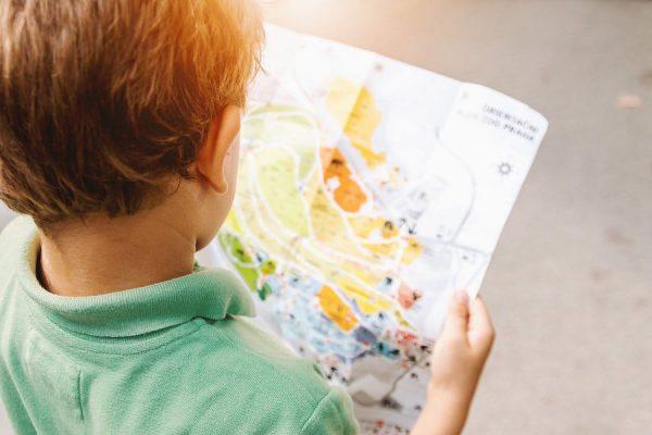Garotinho segurando o mapa de um parque